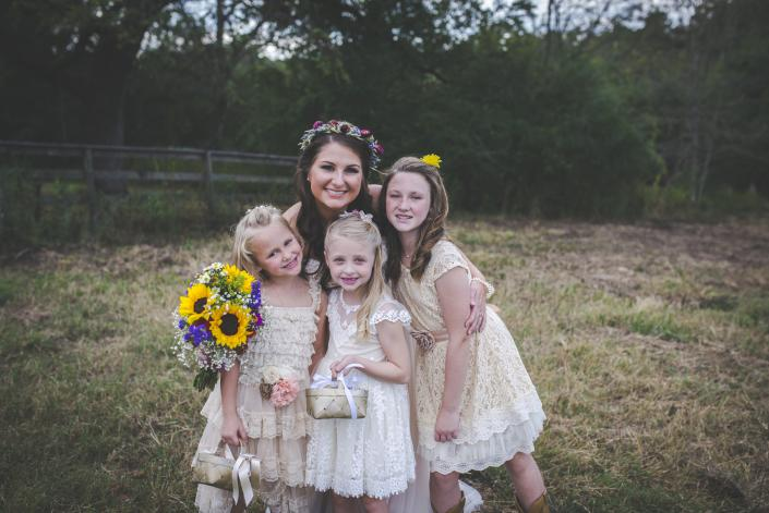 Beautiful bride with pretty petal girls in vintage cream dresses.