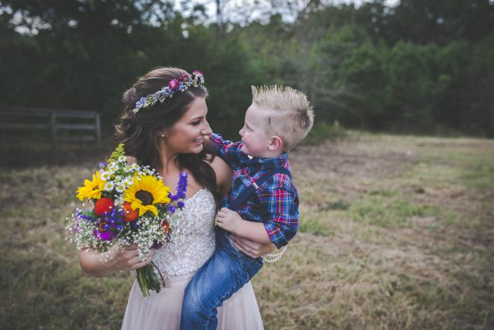 [Image: Beautiful bride in a vintage cream dress with sunflowers and other blooms, lovingly looking at her son. ]