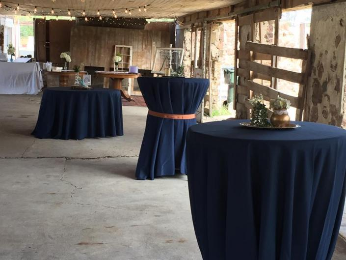 [Image: Round tables with blue tablecloths in contrast with the rustic beauty of the barn, is the perfect combination of vintage and modern.]