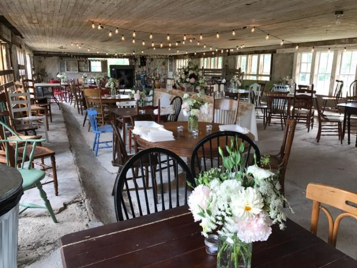 [Image: Lights hanging up in the ceiling and a mix or round and square tables bring this barn to life! Stunning vase arrangements in flowers that are white in color, beautifully add a subtle touch to the rustic environment. ]